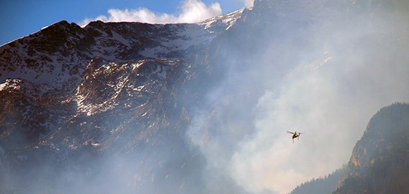 A Type 1 helicopter flies out of a smoky drainage with a craggy mountain in the background.