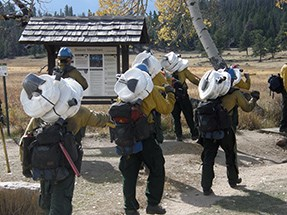 Firefighters start down a hiking trail with coils of hose on their backs.