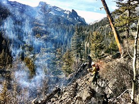 A firefighter hikes in to the confluence of Spruce and Forest Canyons, through steep rocky terrain on November 30.