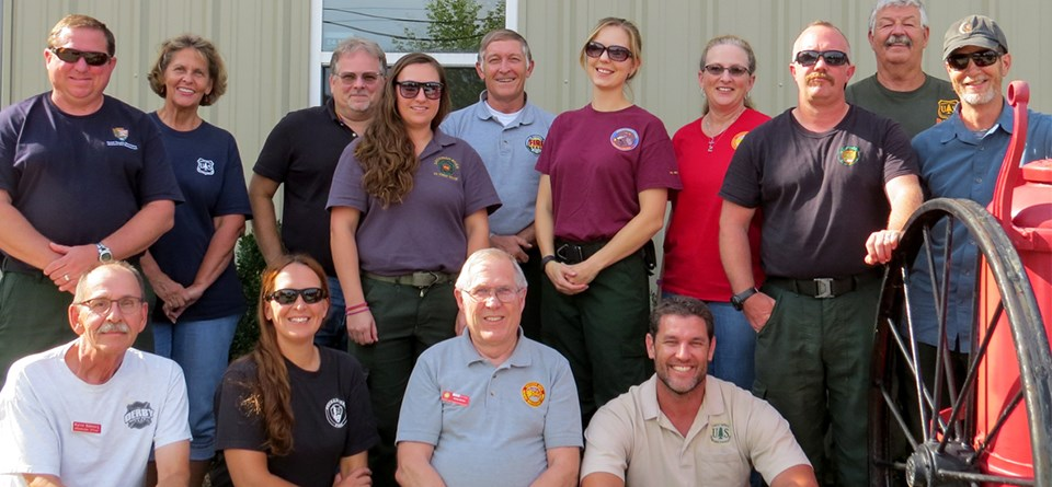 Men and women wearing a variety of agency shirts pose in a group.