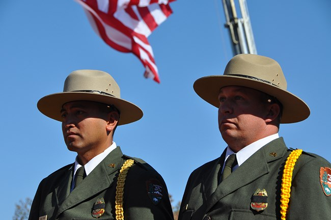 Two men in dress NPS uniform stand beneath a United States flag.