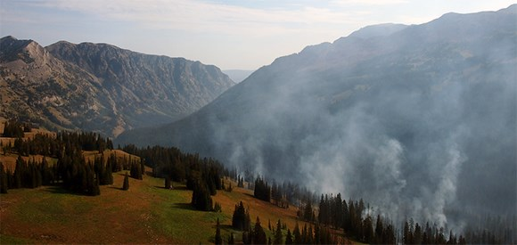 Mountainous terrain with smoke rising from forest in foreground.