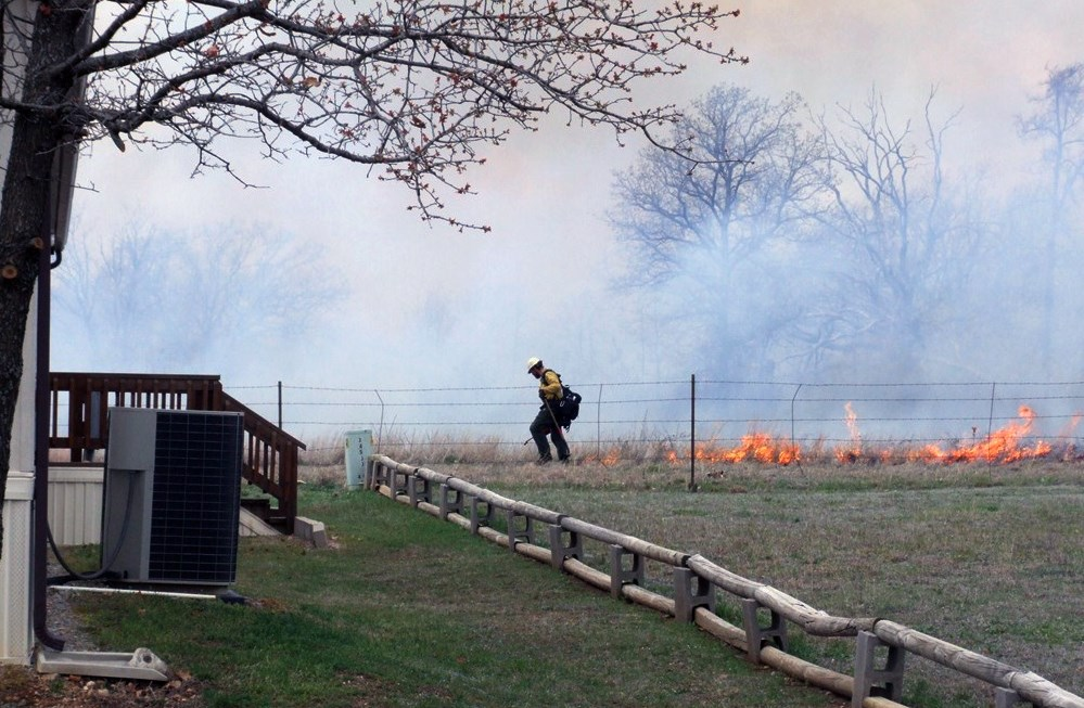 A firefighter uses a drip torch to ignite a prescribed fire along a fenceline.