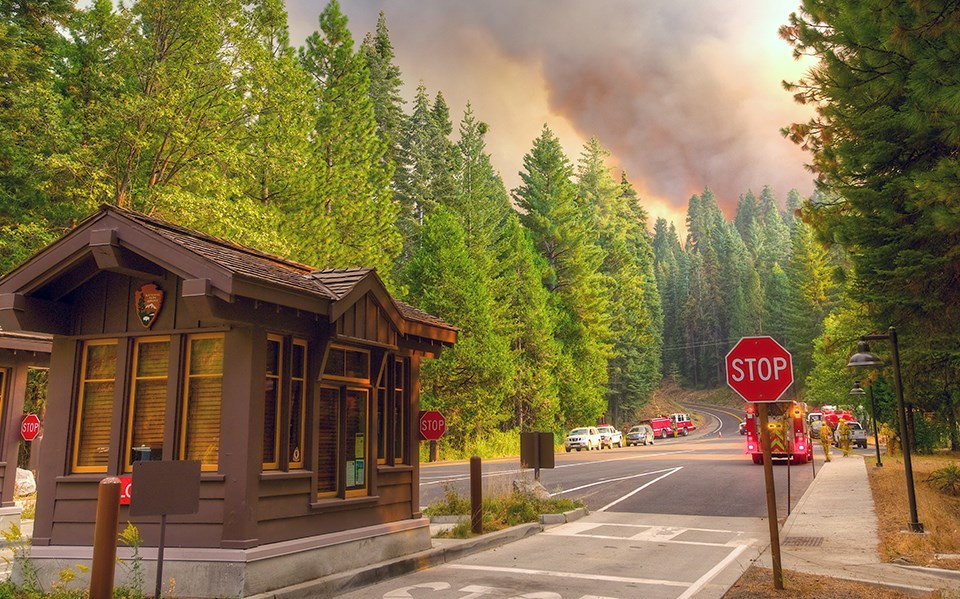 Yosemite park entrance station with a large plume of smoke in the distance.
