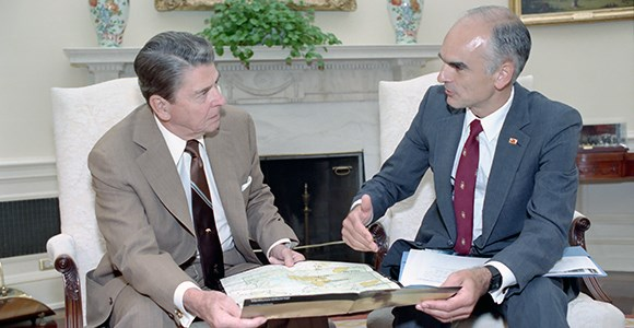 President Reagan holds a map of Yellowstone while looking at Secretary Hodel to his right
