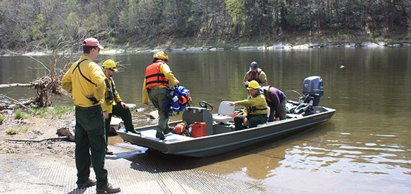 firefighters using a boat to go to a prescribed fire