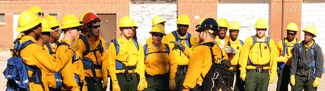 A group of young men and women in firefighting gear listen to a man speaking to them.