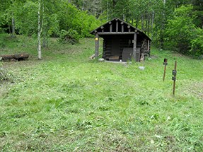 The same cabin as above after vegetation has been cleared--cabin in a clearing.
