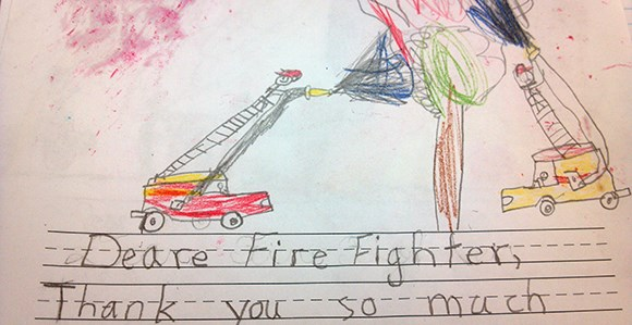 A drawing of firefighters in engines extinguishing a tree. Text below reads: Deare [sic] Fire Fighter, Thank you so much.
