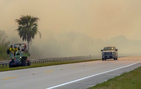 A buggy and firefighters monitor on the side of a road while a truck is on the nearby road.