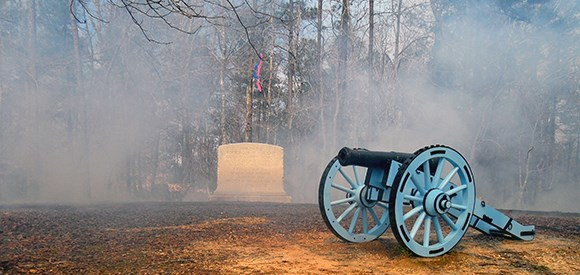 A monument stone is obscured by smoke and surrounded by burned vegetation, while a cannon stands watch in the foreground.