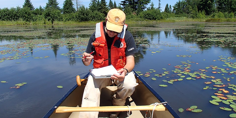 An NPS employee sits in a boat, he is writing on paper