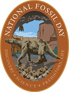 National Fossil Day poster with brown border and scene of prehistoric plants and animals.