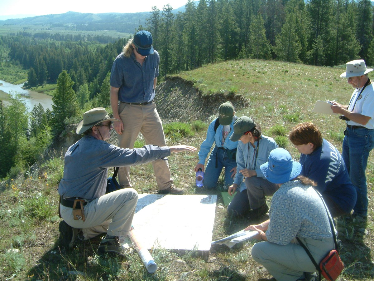 group of people gathered around a map outdoors