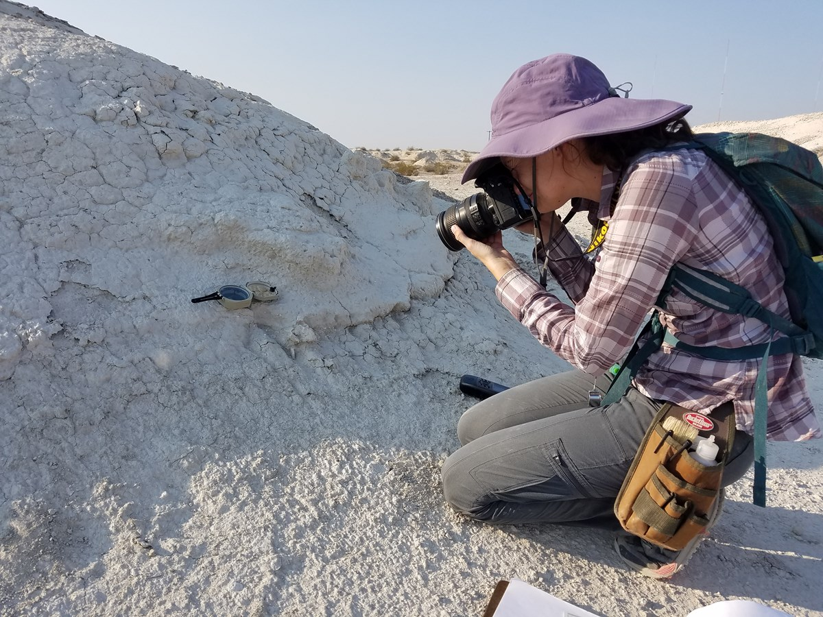 A young woman in a purple hat and sunshirt kneels next to a rock. She looks through her digital camera to photograph a fossil.