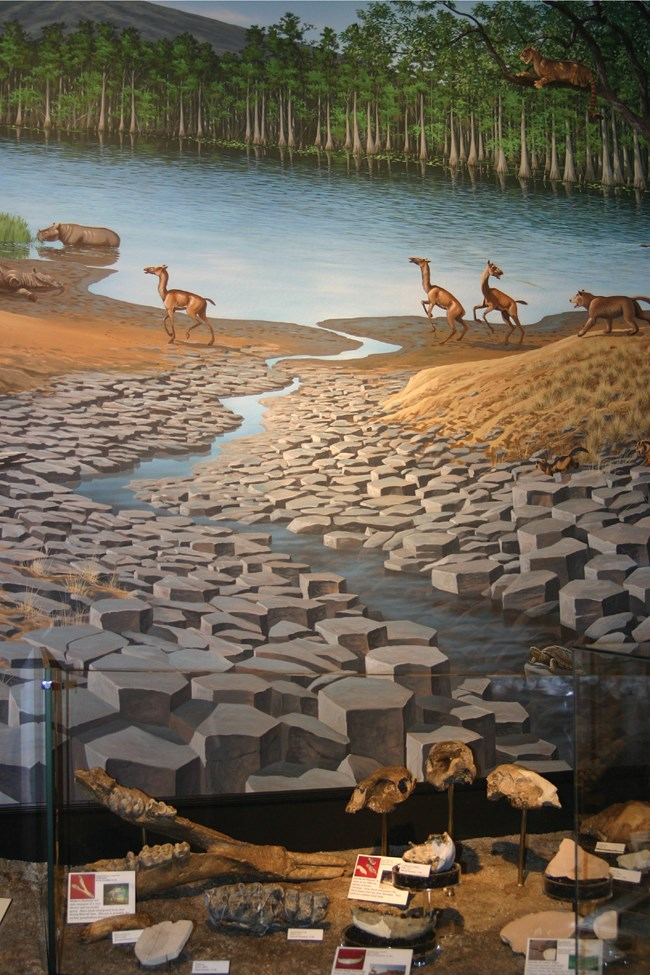 painted mural of prehistoric landscape with columnar basalt and animals