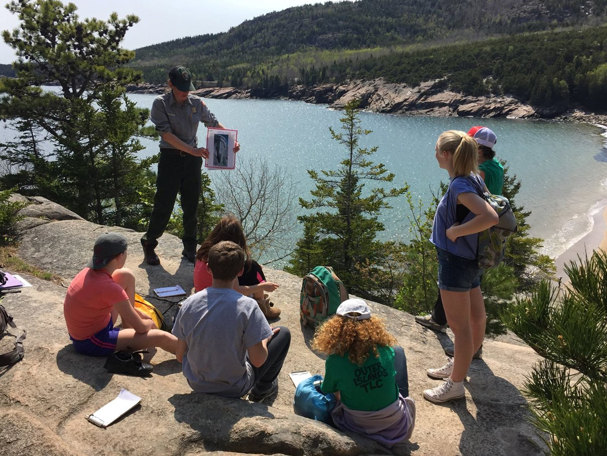 a ranger talking with students on a rocky overlook with ocean and beach below
