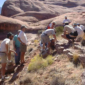 group of people examine rock outcrop