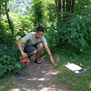 person measuring the width of a trail