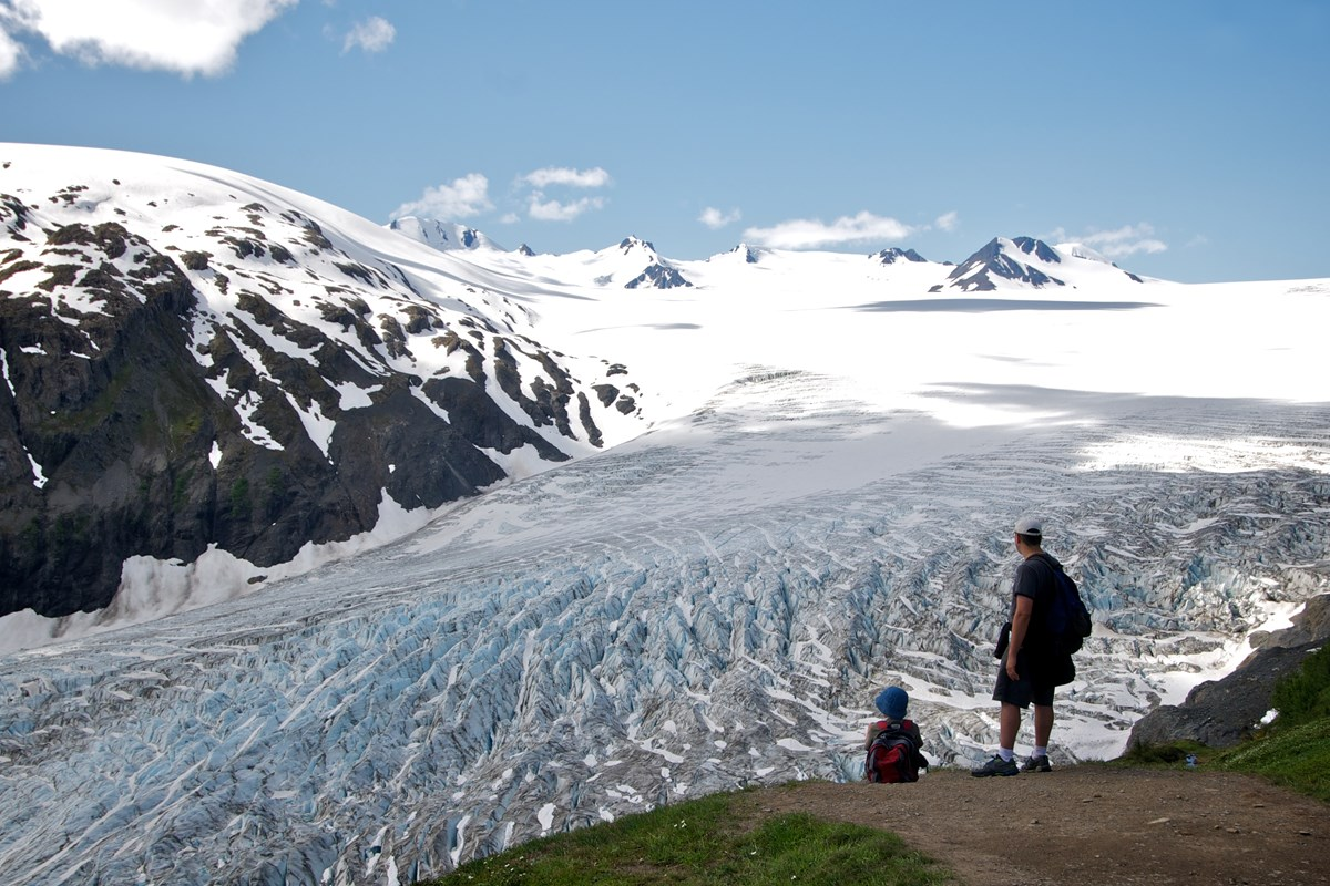 Two people stand next to a dirt trail, looking across Exit Glacier and the Harding Icefield.