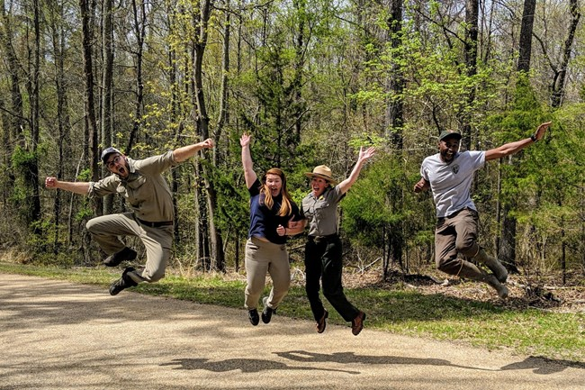 Group of young people jumping for joy in nature.