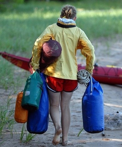 Girls carrying gear and packing up after kayaking