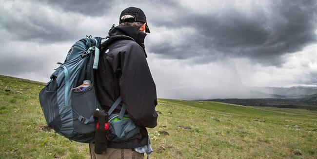 Hiker watches dark storm clouds