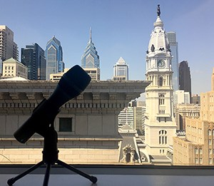 A microphone in front a view of buildings.