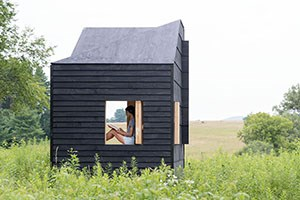 A person sits and writes in a mobile studio in a meadow.