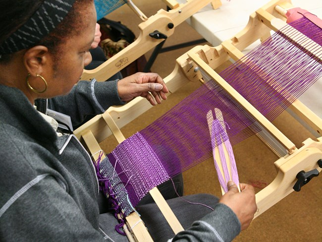 A woman works on a small loom at the John C. Campbell Folk School