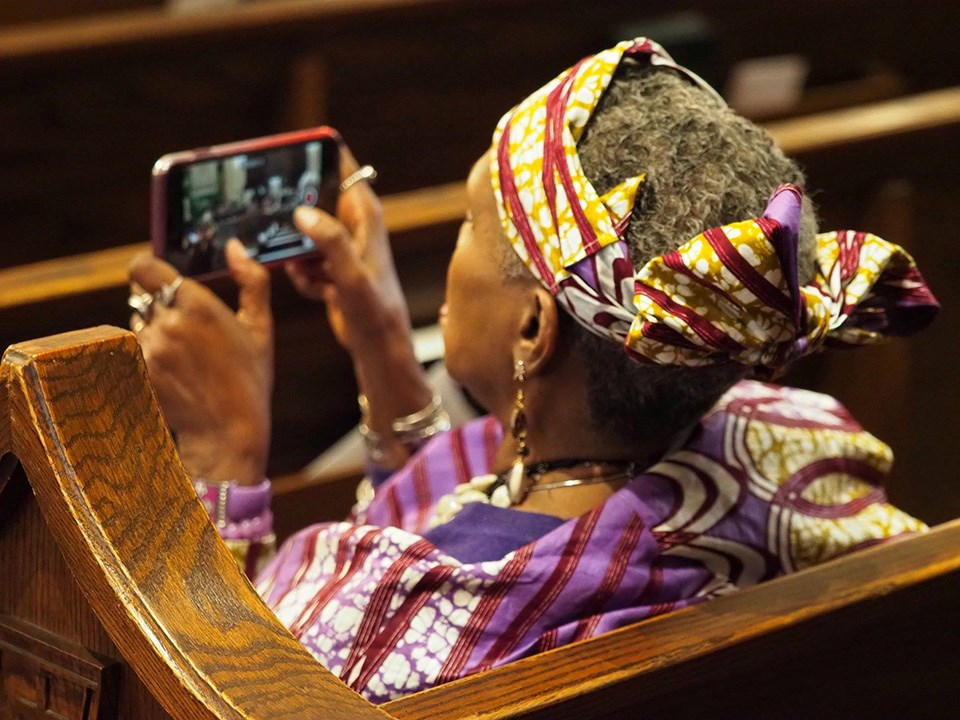Woman in audience recording Watch Night performance with her phone, Morris Brown AME Church, Charleston, SC, 2018