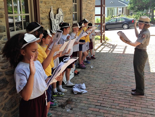 Park ranger swears in a group of Chesapeake Trail Junior Rangers at the Zimmerman Center for Heritage