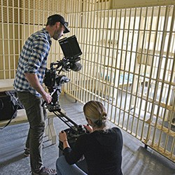 Two people film a jail cell