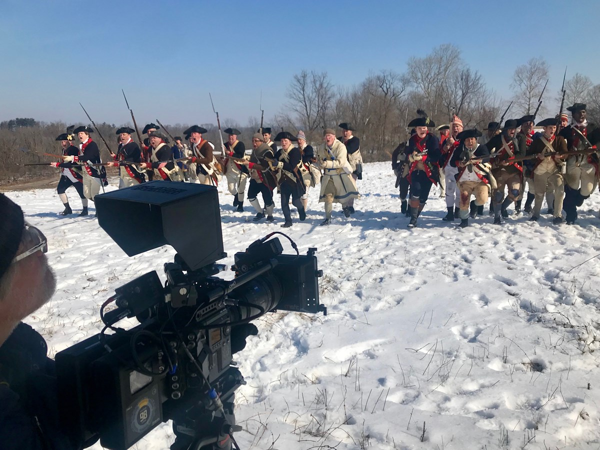 A man holds a camera towards a group of people dressed in revolutionary war costumes coming towards us.