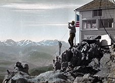 Ranger with binoculars looking out from the fire lookout at Twin Sisters Peaks in Rocky Mountain National Park, 1916. Colored lantern slide.