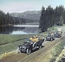 Auto tour passing Sylvan Lake in Yellowstone National Park, 1916. Colored lantern slide by Haynes.