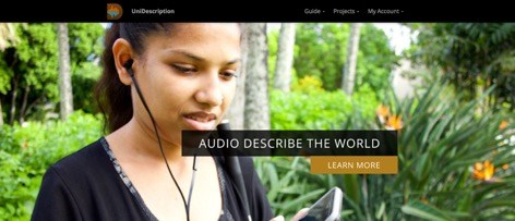 A woman wears headphones that are attached to a mobile device she is holding.  There is lush flora behind her.