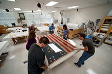 Six people repairing an American flag from the civil war