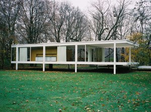 Farnsworth House, with green lawn in foreground and bare trees in the background