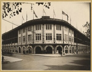 Arched entryway to Forbes Field, with flags flying above the field.