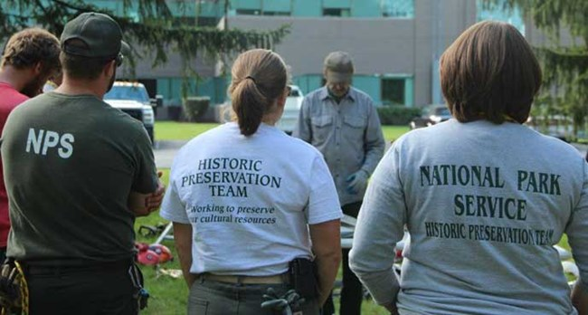 "NPS employees standing around an instructor. The back of their t-shirts read ""Historic Preservation Team."""