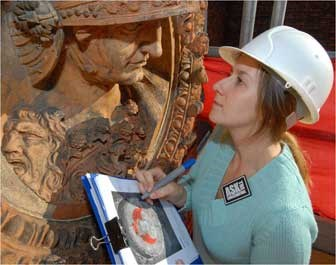 A female intern wearing a hardhat with a clipboard looking closely at a large artifact.