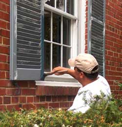 A main repainting a shutter on a historic brick building.