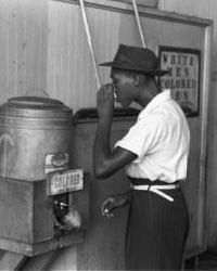Photo of African American man drinking from water fountain marked 'Colored.'