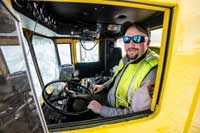 a man in a fluorescent vest drives a snow plow