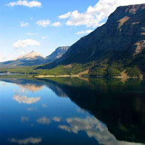 A mountain in Glacier National Park is reflected in a still lake.