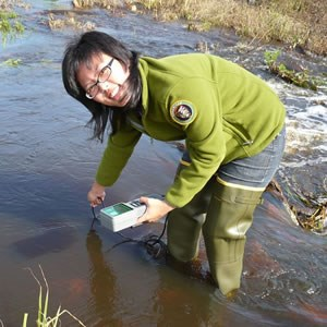 A woman volunteer wearing hip waders, conducts water sampling in a small creek.