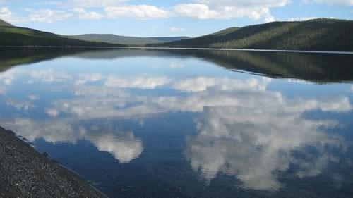 Clouds reflect off of Shoshone lake in Yellowstone National Park.