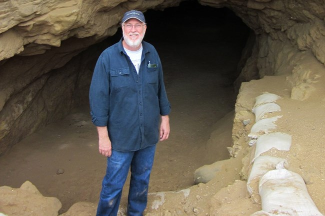 Man in blue shirt and jeans standing in front of cave.