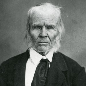 Historic black and white photo of elderly man with white hair in black jacket.
